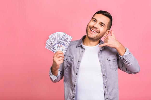 Gelukkige winnaar bel me teken. jonge rijke man in casual bedrijf geld dollarbiljetten met verbazing