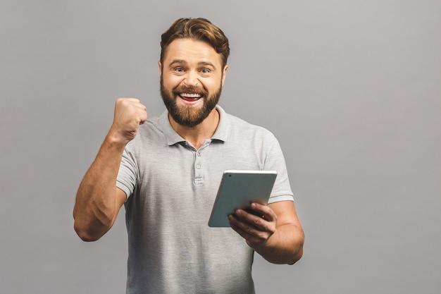 Gelukkige winnaar! berded jonge man in casual staande en met behulp van tablet