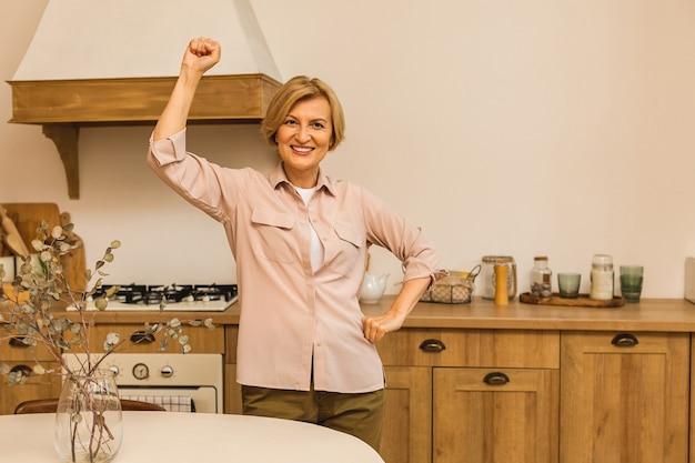 Gelukkige winnaar! close-upportret van mooie bejaarde rijpe oude hogere vrouw in de keuken na het koken.