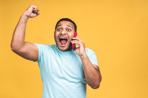 Gelukkige winnaar! foto van een zwarte afro-amerikaanse indiaan die weet dat hij winnaar is geworden van iets dat zo blij is met nieuwsinformatie terwijl hij geïsoleerd is over gele achtergrond.