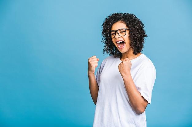 Gelukkige winnaar! foto van vrolijke mooie jonge afro-amerikaanse vrouw geïsoleerd op blauwe muur achtergrond. kijkende camera die winnaargebaar toont.