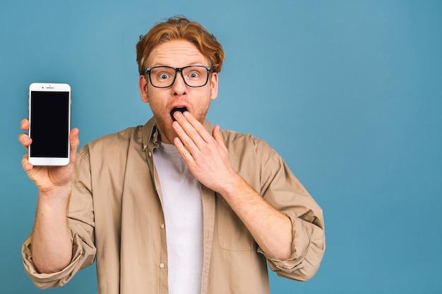 Gelukkige winnaar! jonge knappe geschokte verbaasde man die smartphonescherm met onverwacht gezicht toont