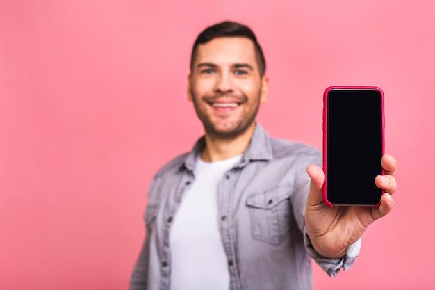 Gelukkige winnaar jonge knappe man smartphone screenwith onverwacht gezicht tonen