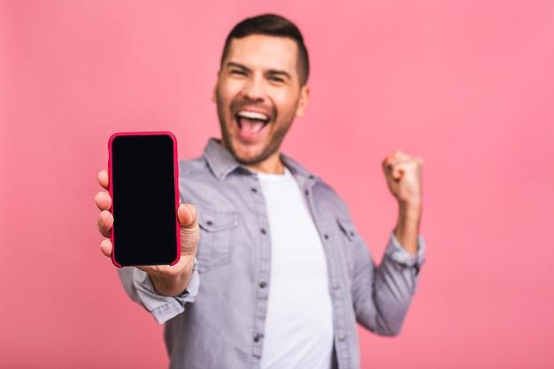 Gelukkige winnaar jonge knappe man smartphonescherm met onverwachte gezicht tonen