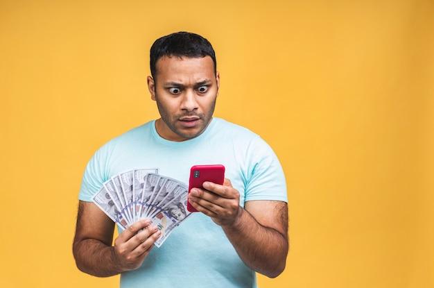 Gelukkige winnaar! jonge rijke afro-amerikaanse indiase zwarte man in casual geld dollarbiljetten en mobiele telefoon met verrassing geïsoleerd op gele achtergrond.