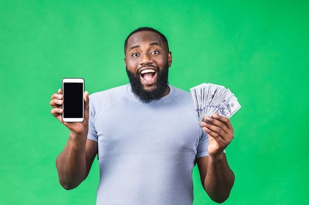 Gelukkige winnaar! jonge rijke afro-amerikaanse man in casual t-shirt met geld dollarbiljetten en mobiele telefoon met verrassing geïsoleerd op groene achtergrond.