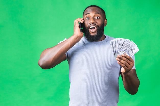 Gelukkige winnaar! jonge rijke afro-amerikaanse man in casual t-shirt met geld dollarbiljetten en mobiele telefoon met verrassing geïsoleerd over groene muur.
