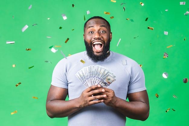 Gelukkige winnaar! jonge rijke afro-amerikaanse zwarte man in casual t-shirt met geld dollarbiljetten met verrassing geïsoleerd over groene achtergrond.