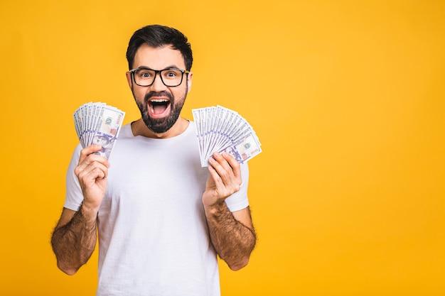 Gelukkige winnaar! jonge rijke man in casual bedrijf geld dollarbiljetten met verrassing geïsoleerd op gele achtergrond.