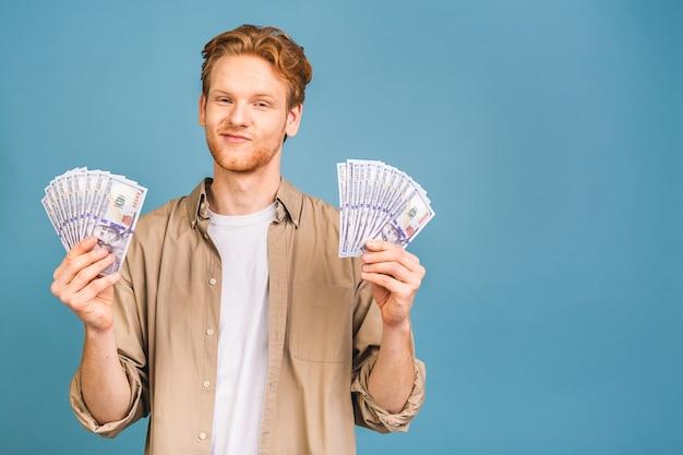 Gelukkige winnaar! jonge rijke man in casual geld dollarbiljetten met verrassing