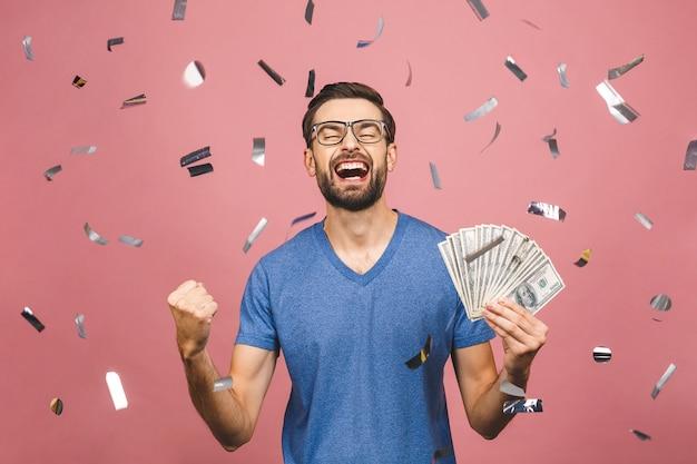 Gelukkige winnaar! jonge rijke man in casual t-shirt met geld dollar biljetten met verrassing geïsoleerd op roze achtergrond.
