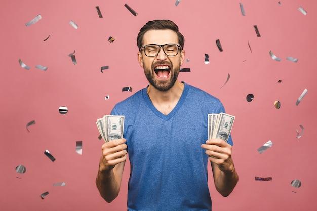 Gelukkige winnaar! jonge rijke man in casual t-shirt met twee fans van geld dollarbiljetten met verrassing geïsoleerd op roze achtergrond.