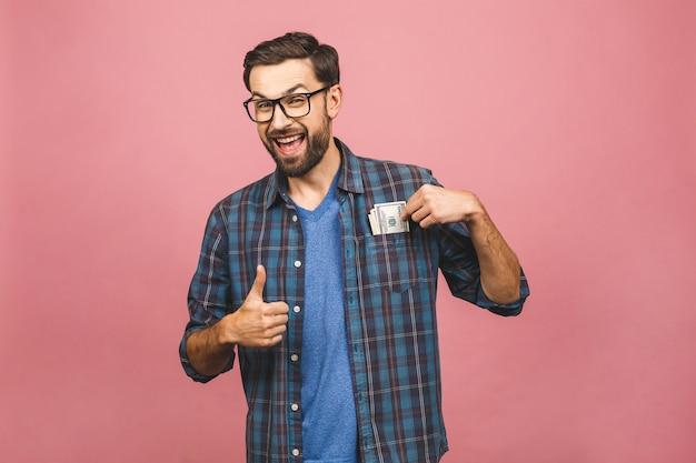 Gelukkige winnaar! jonge rijke man in het geruite overhemd van de het gelddollar van de overhemdsholding in de zak met verrassing die over roze achtergrond wordt geïsoleerd.