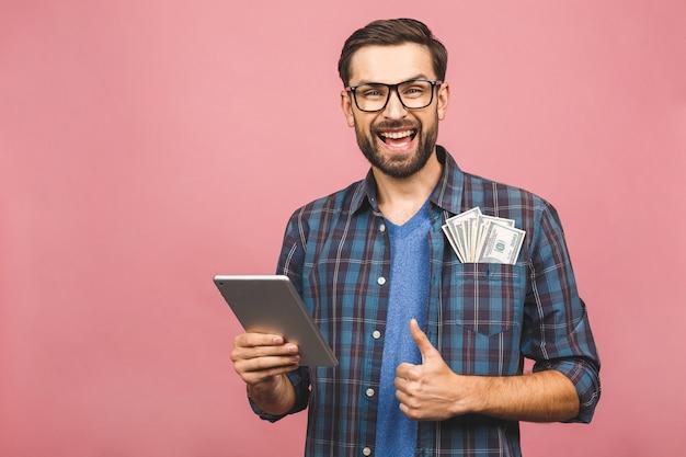 Gelukkige winnaar! jonge rijke man in toevallige de dollarrekeningen van het holdingsgeld en tabletcomputer met verrassing die over roze muur wordt geïsoleerd. duimen omhoog.