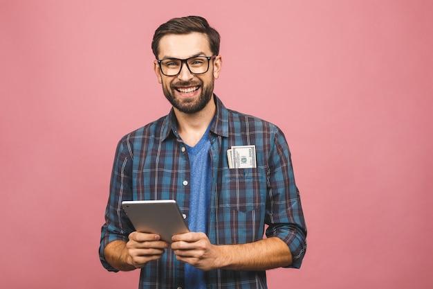 Gelukkige winnaar! jonge rijke man in toevallige de dollarrekeningen van het holdingsgeld en tabletcomputer met verrassing die over roze muur wordt geïsoleerd.