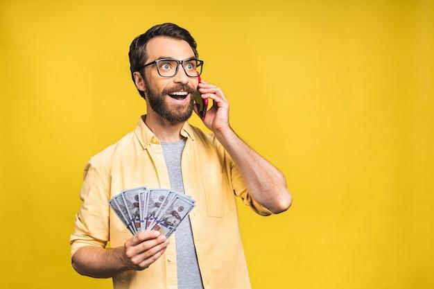 Gelukkige winnaar! opgewonden jonge, bebaarde man in casual met veel geld in dollarvaluta's en het gebruik van mobiele telefoon in handen geïsoleerd op gele achtergrond.