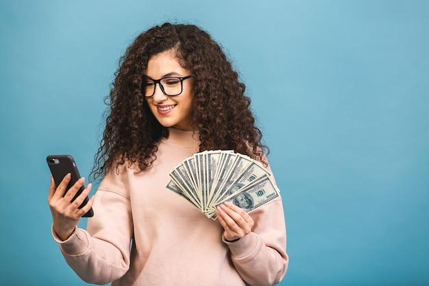 Gelukkige winnaar! portret van een vrolijke jonge krullende vrouw met geld bankbiljetten en vieren geïsoleerd op blauwe achtergrond. met behulp van telefoon.