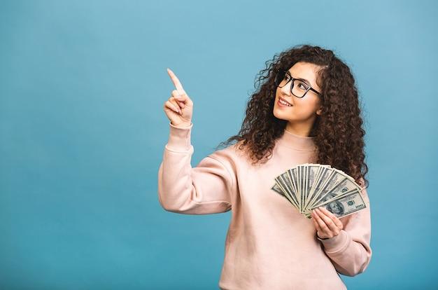 Gelukkige winnaar! portret van een vrolijke jonge krullende vrouw met geld bankbiljetten en vieren geïsoleerd op blauwe achtergrond. wijzende vinger.