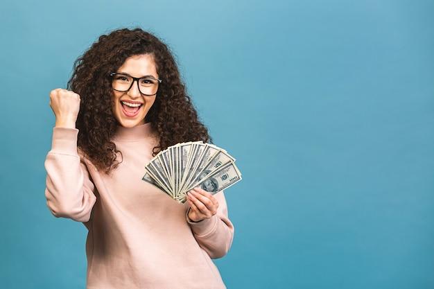 Gelukkige winnaar! portret van een vrolijke jonge krullende vrouw met geld bankbiljetten en vieren geïsoleerd op blauwe achtergrond.