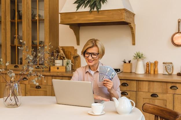 Gelukkige winnaar. vrolijk lachende bejaarde senior vrouw die in de keuken staat en haar laptop en geldrekeningen gebruikt, freelancer die thuis werkt.