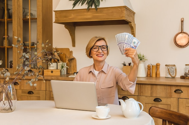 Gelukkige winnaar. vrolijk lachende bejaarde senior vrouw die in de keuken staat en haar laptop en geldrekeningen gebruikt, freelancer die thuis werkt. Premium Foto
