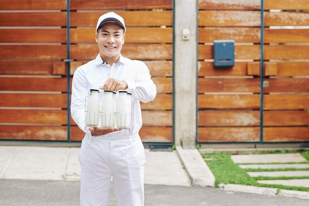 Gelukkige yuong aziatische melkboer die verse melk in glasflessen aanbiedt