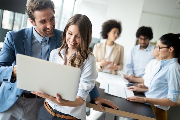 Gelukkige zakelijke collega's in moderne kantoren die samenwerken