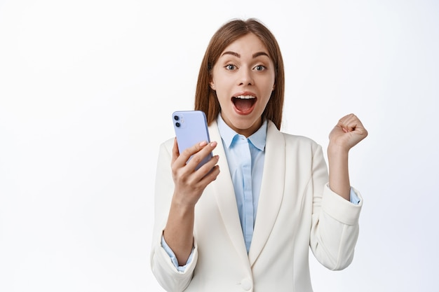 Gelukkige zakelijke vrouw schreeuwt van vreugde, wint op mobiele telefoon, triomfeert van goed nieuws op internet, houdt mobiele telefoon vast en springt van geluk, witte muur
