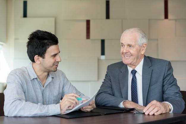 Gelukkige zakenlieden die overeenkomst in bureau bespreken