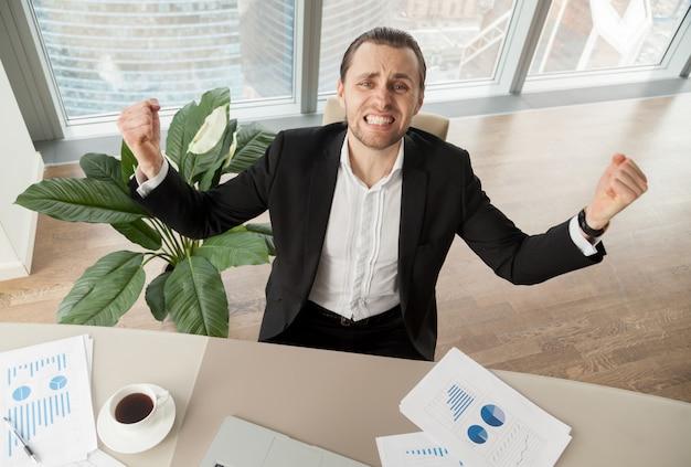 Gelukkige zakenman bij bureau het vieren verwezenlijkingen