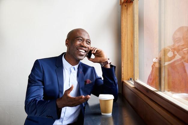 Gelukkige zakenman bij een koffie die op celtelefoon spreekt