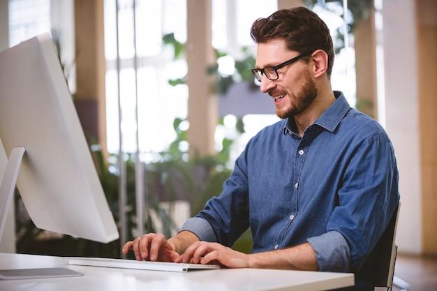 Gelukkige zakenman die aan computer op creatief kantoor werken