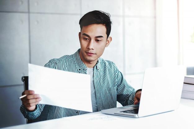 Gelukkige zakenman die aan laptop en documentdocument werkt in bureau