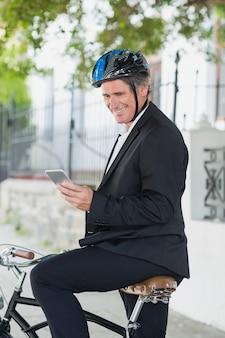 Gelukkige zakenman die cellphone op fiets gebruiken