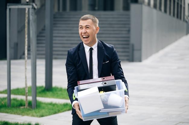 Gelukkige zakenman die de straat loopt met een doos met spullen als het verlaten van het zakencentrum en dansen