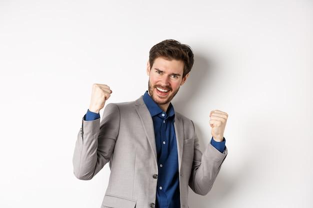 Gelukkige zakenman die geldprijs wint, zeg ja en lachend opgewonden, maak vuistpomp-teken om de overwinning te vieren, zegevierend in pak op witte achtergrond.