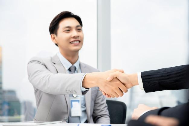 Gelukkige zakenman die handdruk met onderneemster maken bij vergaderzaal in stadskantoor