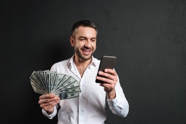 Gelukkige zakenman die het mobiele geld van de telefoonholding gebruiken.