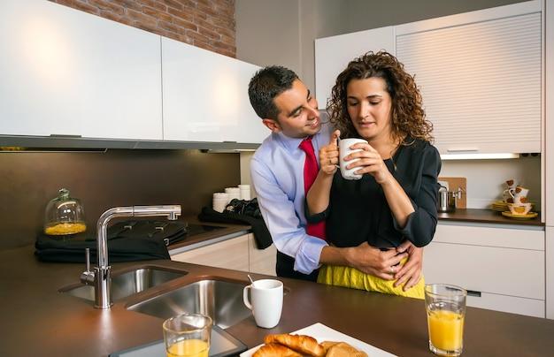 Gelukkige zakenman die krullende vrouw omhelst terwijl hij snel ontbijt voordat hij naar zijn werk gaat