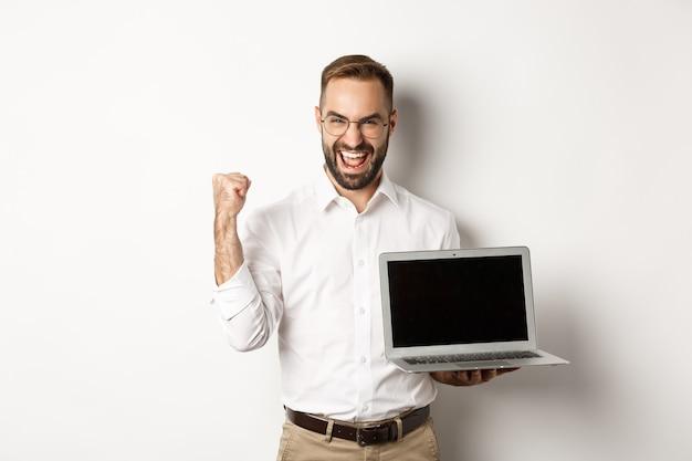 Gelukkige zakenman die laptopscherm toont, vuistpomp maakt en zich verheugt over online prestatie, staande op een witte achtergrond.
