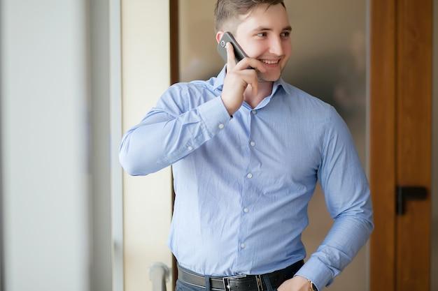 Gelukkige zakenman die op de telefoon op kantoor spreekt