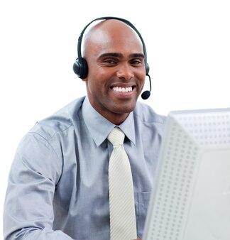 Gelukkige zakenman die op hoofdtelefoon bij een computer spreekt