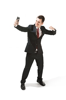 Gelukkige zakenman die op telefoon over wit in studio het schieten spreekt.