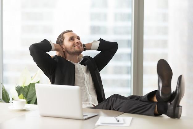 Gelukkige zakenman die over goede perspectieven denkt