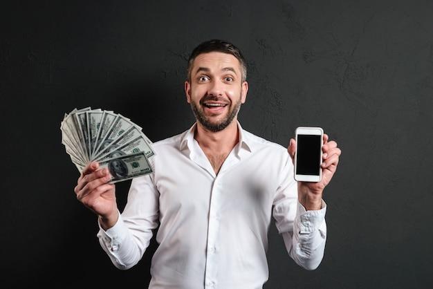 Gelukkige zakenman die vertoning van het mobiele geld van de telefoonholding tonen.