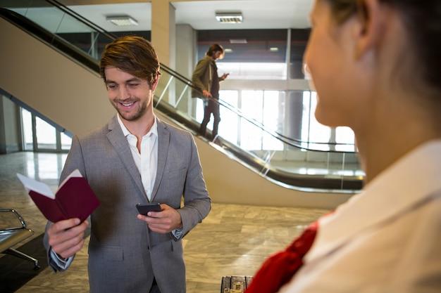 Gelukkige zakenman die zijn paspoort bekijkt terwijl status