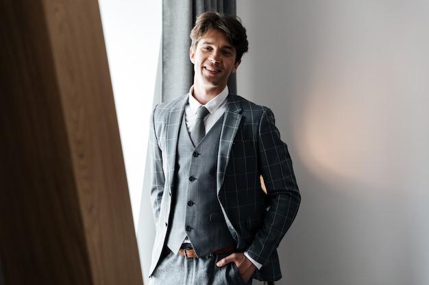 Gelukkige zakenman in en kostuum die bevinden zich glimlachen