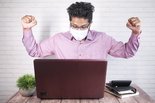 Gelukkige zakenman in gezichtsmasker die aan laptop werkt