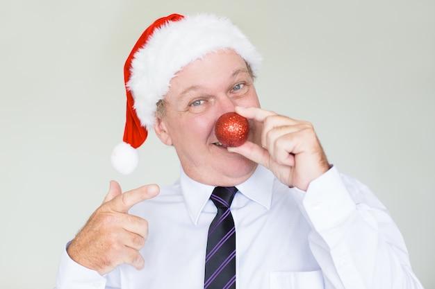 Gelukkige zakenman in kerstmanhoed met rode snuisterij