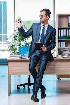 Gelukkige zakenman met geldzakken in het bureau